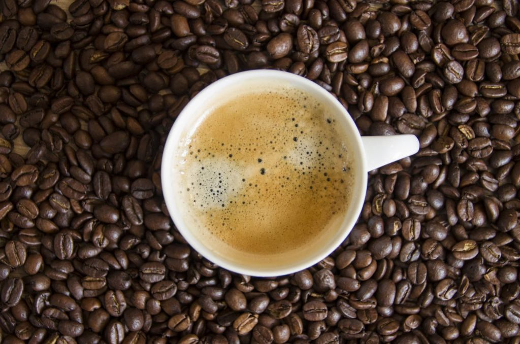 cup of coffee with crema surrounded by coffee beans